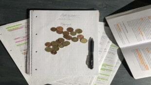 Kleingeld_zusammenrechnen_zwischen_Lernunterlagen_und_Büchern