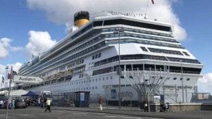 Unter blauem Himmel liegt der große Passagierschiff Costa Pacifica im Kieler Hafen. Im Kreuzfahrtterminal warten die Passagiere auf ihre Einschiffung.