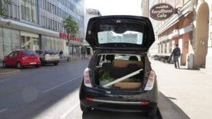 Ein kleines schwarzes Auto parkt auf der rechten Straßenseite in der Stadt. Der Kofferaum steht offen und man sieht darin verstaute Einrichtungsgegenstände.
