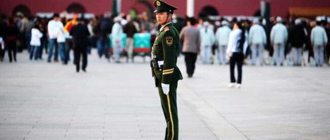 Ein chinesischer Militärpolizist steht auf einem Platz in Peking und überwacht das Geschehen. Im Hintergrund sieht man einige Menschen vor einem Gemälde von Mao Zedong stehen.