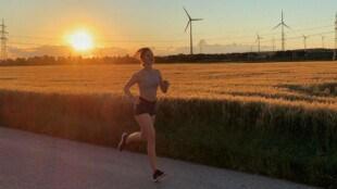 Eine Frau die gerade bei Sonnenuntergang läuft, im Hintergrund ist ein Feld zu sehen
