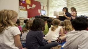 Schulkinder sitzen am Boden im Klassenzimmer und hören zu, während die Lehrerin ein illustriertes Buch vorzeigt.